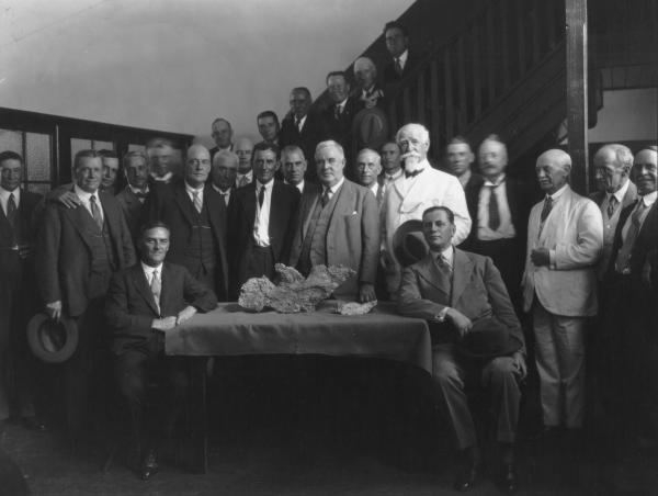 Golden Eagle nugget with Mayor Ben Leslie and men - Claude de Bernales seated right, Jim Larcombe left, finder,  standing behind nugget - Jack Scadden, Minister for Mines,Sir James Mithell Premier for WA,  Ben Leslie Mayor of Kalgoorlie, Ernest Williams Manager of Boulder Perserverance Mine, Info from 'The Mile that  MidasTouched'