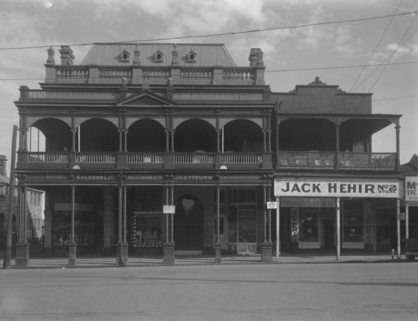 Mechanics Institute & Jack Hehir's No 2 store, Hannan St.,  2 storey buildings with front verandahs - Les Ellis Hairdresser, A Macrow and Sons, GM Tea and Grill Rooms, Central Garage, Dry Cleaner, Garage, 4 cars, people in distance.