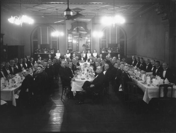 Large dinner party at Palace Hotel, de Bernales,  men and women seated at tables.