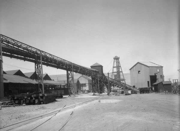 Great Boulder Goldmine, overhead ramp, corrugated iron building, poppet head, railway tracks in foreground.
