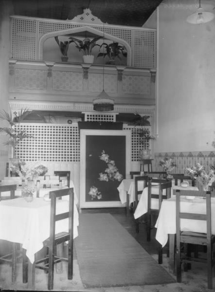 Interior of Cafe, Mechanics Institute Building (Costello(, showiing tables set for a meal, chairs, mat on floor, Chinese style screen, pot plants - some on high trellis-type room divider.