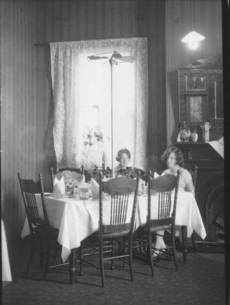 Two women sitting at dinner table in dining room, fan in middle of table. (Reeves)