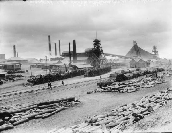 Great Boulder Mine, surface view with main shaft headframe, corrugated iron buildings, smoke stacks.  Rail tracks and stacks of timber in foreground.