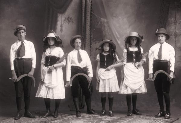 Studio group  of young man and girls in 'Harvester'theme costumes carrying sheaves and sickles.