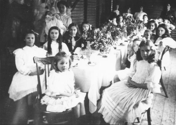 Children seated on house verandah(?) at a long table decorated for a party. Party dresses - frilled lace etc. VICKERS