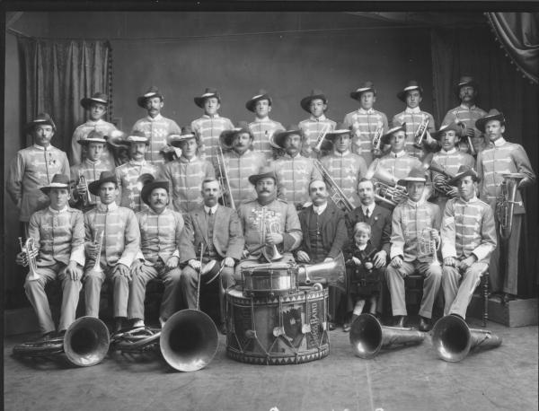 Studio group; men with brass musical instruments and 'military' style uniforms and digger hats. Bass drum decorated withh black swan and 'Boulder City Brass Band'