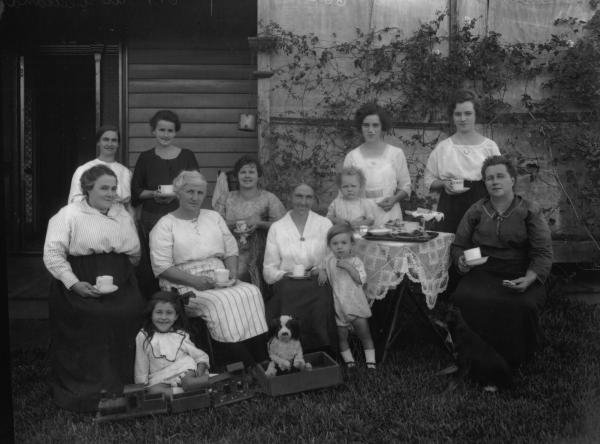 Group of women and children taking tea outside clapboard house. Hessian screen on verandah. Dog right front. Children's toy train and stuffed dog centre left. Lace cloth and cake stand on small table. Assorted cups.
