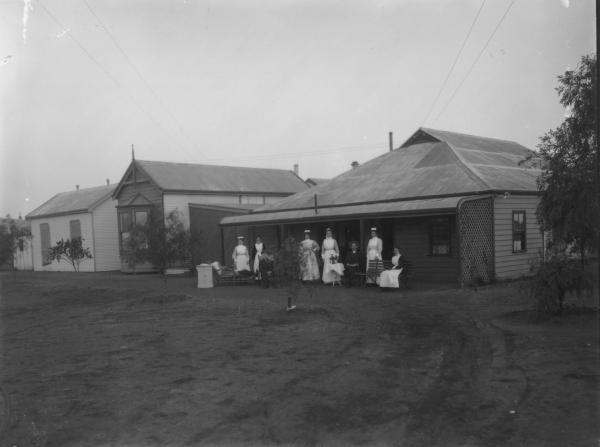 Six nurses and three patients outside Nurse Egan's hospital. Electricity supply wires visible.