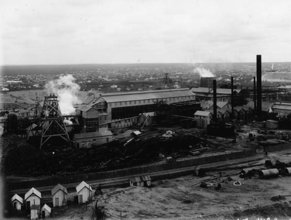 View of minesite with Boulder City in background. Wood stack and rail track in foreground. Miners' canvas / hessian houses also in left foreground.