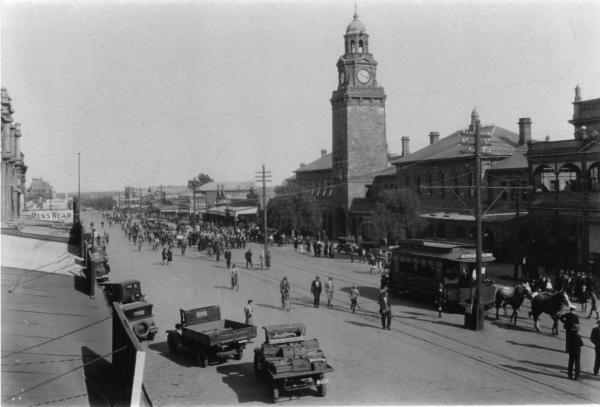 Hannan St, viewed from Maritana St., Many people and cars coming up street, tram, horses, cars and bicycles in street. 1908