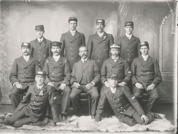 Portrait of group of eleven men of South Kalgoorlie Fire Brigade in uniform. Davidson Brothers.  Man seated in front is HW Davidson.