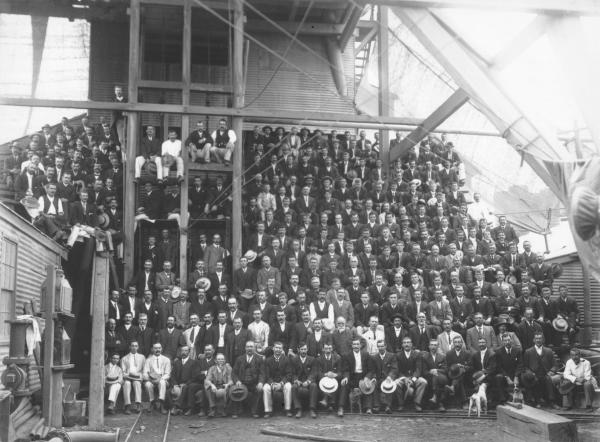 Large group of miners and staff at Kalgurli Goldmine sitting under headframe, most have taken off hats and are holding them.Frederck George Brinsden (Born 1980 in Creswick Vic, died 1958) is second on left in front row.