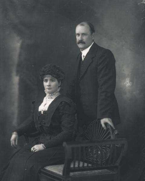 3/4 portrait of woman seated and man standing, both wearing formal black clothes, woman with jewellry. 'Mr. A.E. Sharland'