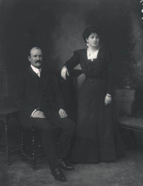 F/L portrait of man seated and woman standing, both wearing formal black clothes, woman with jewellry. 'Mr. A.E. Sharland'