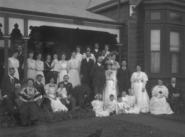 F/L portrait of large wedding group (32) including 7  children on verandah of house 'Craigross'. F.W. Daniels.