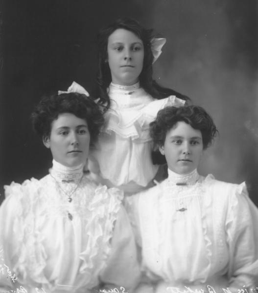 1/2 portrait of three young women, dressed in white high necked dress, jewellry. Miss N. Burkett.