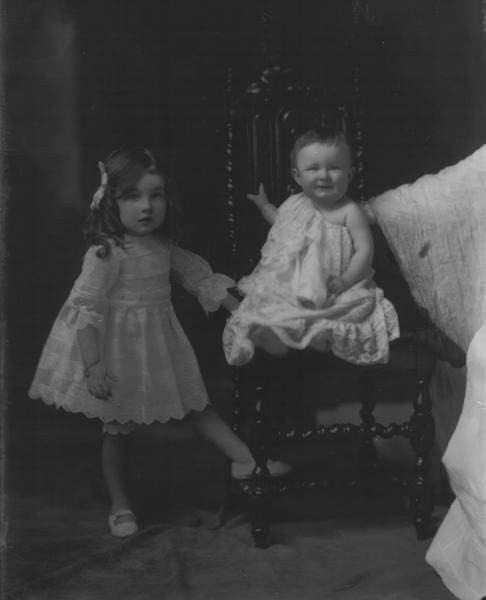 F/L portrait of 2 young children. Girl standing  wearing short dress, baby seated wearing long lace gown. Mrs. C. Reeves.