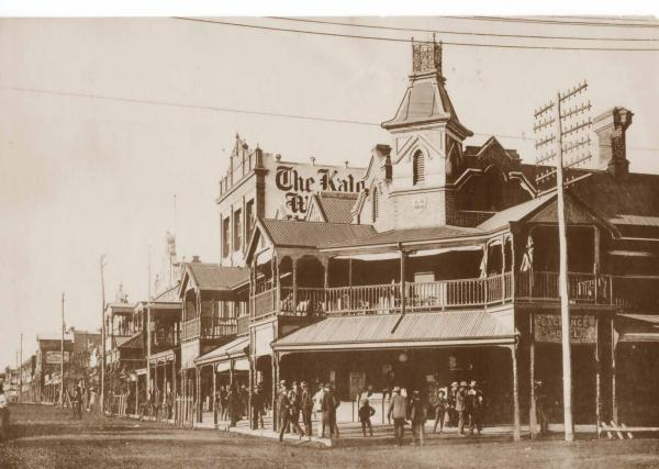 Exchange Hotel, corner of Hannan Street and Maritana St looking up towards Mt Charlotte.  Several men and boys standing outside, Hocking (Kalgoorlie Miner) building in background.  1900