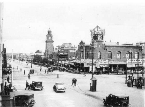 Intersection of Hannan and Maritana Streets looking towards the post office.  Shows the Mechanics Institute and McKenzie Building.  Shows lots of motor vehicles and people standing on street corners.