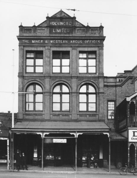 Hocking & Co building (Kalgoorlie Miner) Hannan Streeet, Kalgoorlie.  Shows part of Exchange Hotel on right.  Few men and boys standing outside.