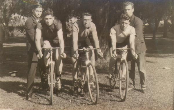 Three men on racing bikes with two men standing. Menzies to Kalgoorlie bike race  Far left holding bike Keith Hudson, on bike Ron (Tim Hudson).  Middle on bike Jack M Trouchet.  Man standing on right Tom Ford holding Barry Bracegirdle on bike.  Info supplied by John Terrill and Elva Hudson.