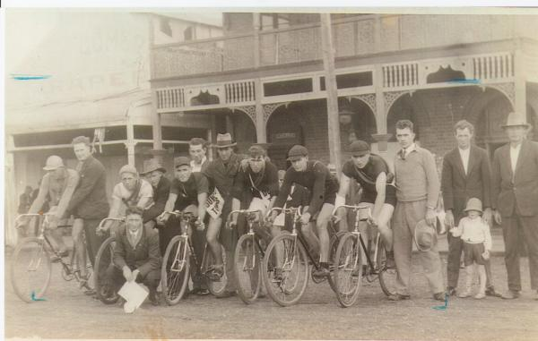 Menzies to Kalgoorlie Bike race taken outside Grand Hotel, Menzies. 6 men on racing bikes with several other men and one child.  Montgomery's store in the background.