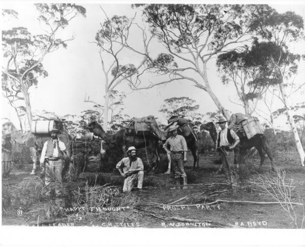 Four prospectors A G Black, C H Stiles, H W Johnston, B A Boyd standing in front of 4 loaded camels in bushland. Men are suitably and tidily dressed for a prospecting trip - waistcoats, hats, neck-scarves, boots. 'Happy  Thoughts Prospecting Party'