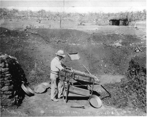 Man with dryblower, gold pan and sieves by low rock wall (entrance to mine?) Building with thatched roof in background. Coolgardie