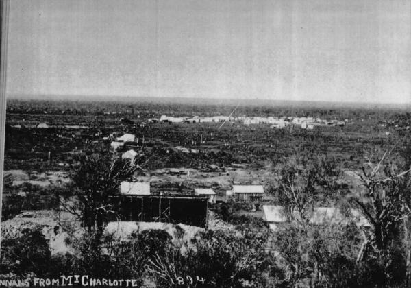 'Hannans from Maritana Hill'. Mining in progress in foreground with tents among dumps and sparce vegetation. Some more subtantial housing in background.