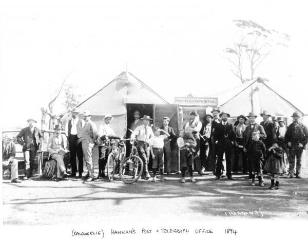 Group of men and children outside 'Post Telegraph Office'Two men have push bikes. Building made from hessian and wood.