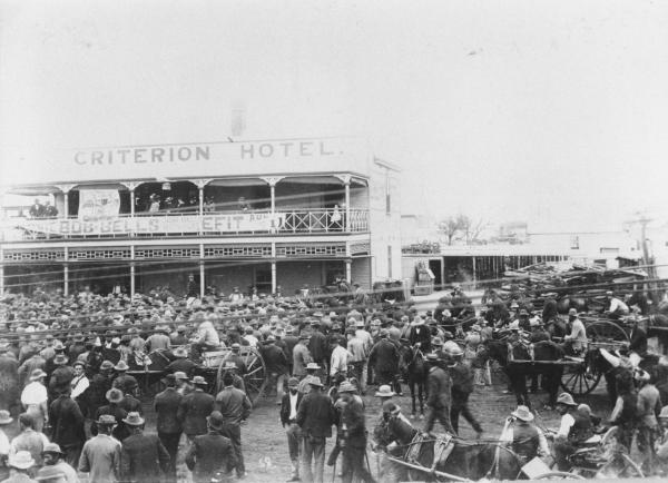 Large crowds of people outside 'Criterion Hotel' waiting for Father Long to announce the 'Sacred Nugger' found at White Feather Kanowna. Horses and carts among the crown waiting.