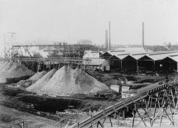 'Great Boulder GM'- large buildings with timber framework and corrugated iron, poppet heads, treatment plant, chimneys, elevated railway line.