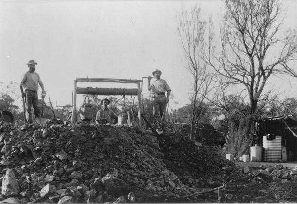 Three men standing on mine workings with hand winder, bucket and various tools, low store shed by shaft and rain  water tank.