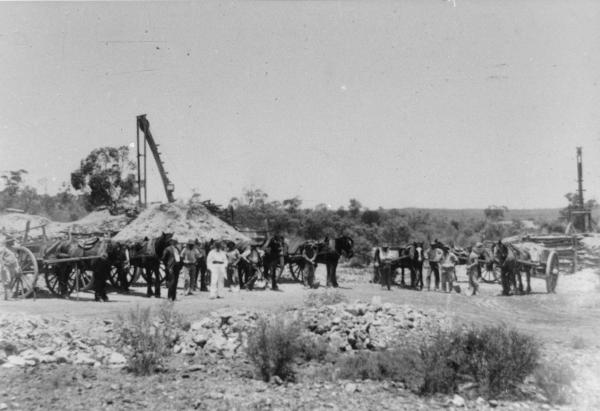 Men with horses and carts posing by 2 small mines, mackine 'poppet heads', slag heaps. Most men in working clothes with shovels, one man in suit and hat, another in white pants and coat and bandana type belt posing in centre of line.