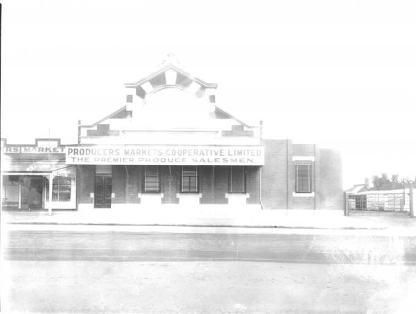 Front view of 'Producers Market' building set on road with tramline. Big sign saying 'Producers Markets Co-Operative Limited, the premierproduce salesmen'. Another store is adjacent 'Paull Bros.' Gate into yard at right.