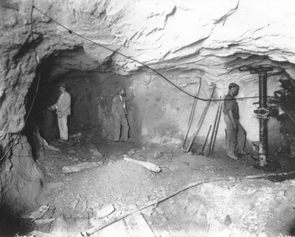 Mine, underground, 3 men, mining tools propped by wall, hoses, air pipes, candles.