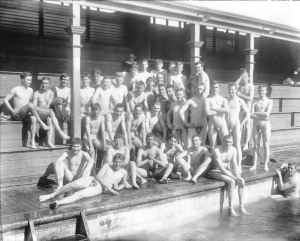 Group of naked men/boys posed on seats of stand by Kalgoorlie's first swimming pool in Victoria Park.