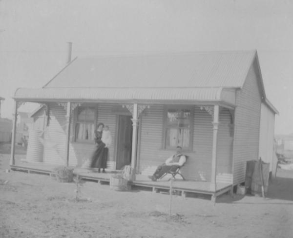 House in Trafalgar, Man seated in chair  Douglas William GRAY and woman standing holding small child May Elizabeth nee Gilholm. House is small cottage with iron roof and bull nose verandah, two planters at front water tank at side, Donated by Jessie GRAY, daughter of Douglas GRAY.