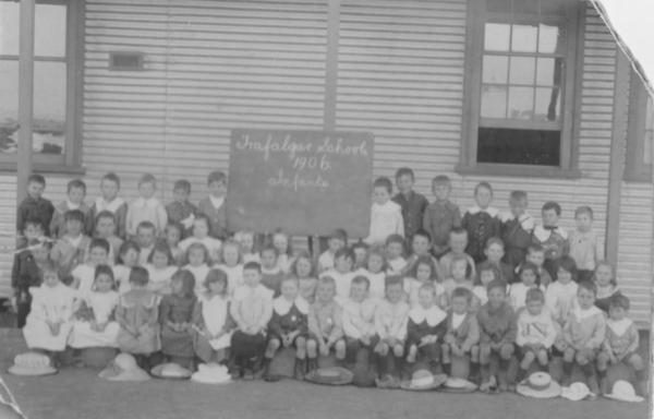 Trafalgar School Infants 1906. Formal schoo photo, children in best clothes seated outside school building. Donated by Jessie GRAY woh attended the school with her brother D W Gray.