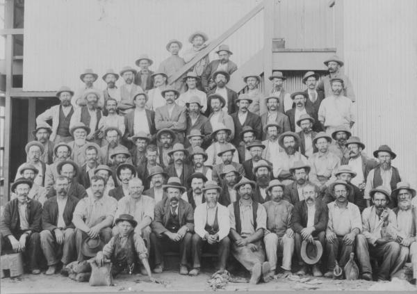 Lake View and Star Miners, 1900 Douglas William GRAY third row from top with arms folded.  Donated by his daughter Jessie GRAY.  Semi formal photo taken outside mine building, two water bags in foreground.