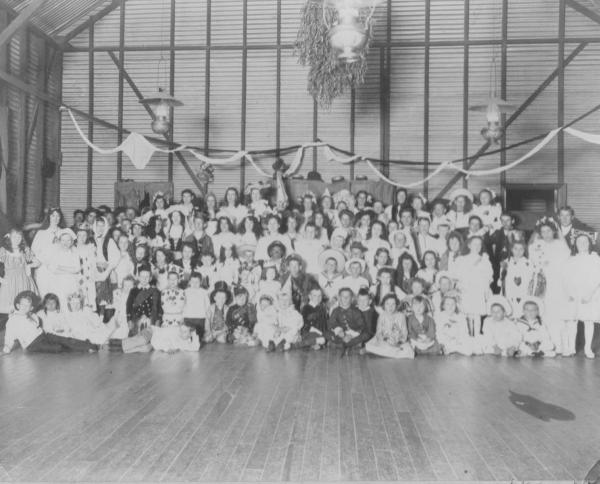 Fancy Dress Ball at St Lukes Church Trafalgar held in church hall on 3rd October 1906. Donated by Jessie GRAY  (in photo) shows corrugated iron walls with three kerosene lamps hanging from ceiling.