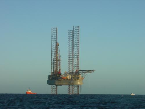 Deep sea oil rig in the ocean with small red ship sailing past.