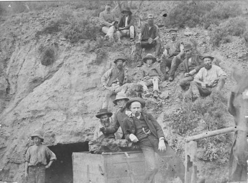 Men standing on a hill at entrance to a coal mine B/W.