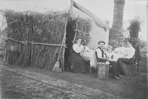 Traditional homestead, smartly dressed family enjoying dinner around table B/W.