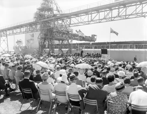 A seated crowd outside watching the Premier on stage B/W.