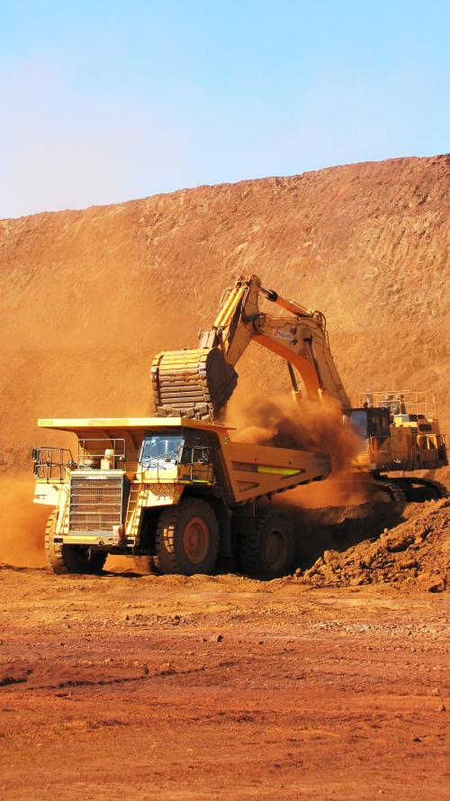Dump Truck being loaded by a digger in an open air mine.