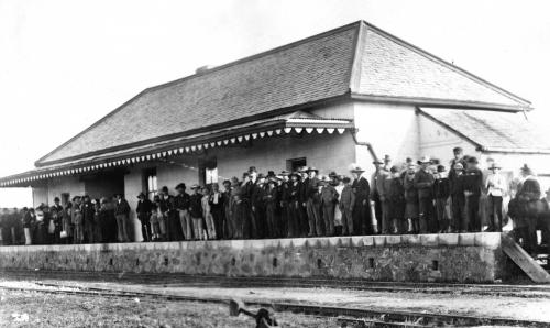 Many people waiting for the train at Northampton station B/W.