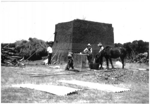 4 men and a horse working in front of a square brick Kiln about 14ft high B/W.