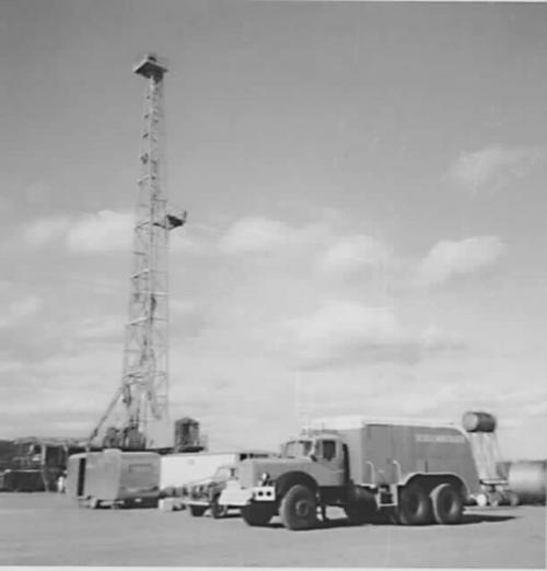 1964 Oil rig with a fleet of vehicles in the front of the shot B/W.