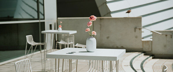 Image showing white table and chairs with flowers in an outdoor balcony setting